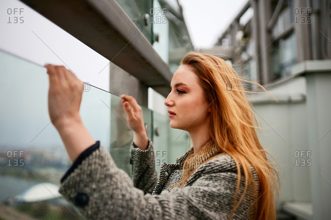 Woman holding glass while standing on the balcony