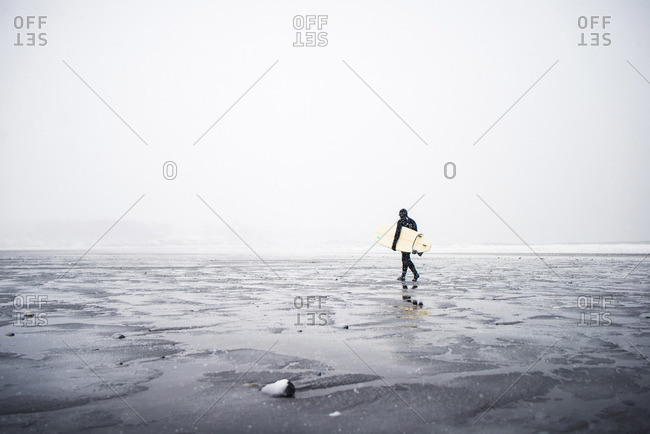 Surfer walking along the beach in Maine during a winter snow storm