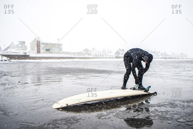 Surfer checking the bottom of board during a Maine snow storm