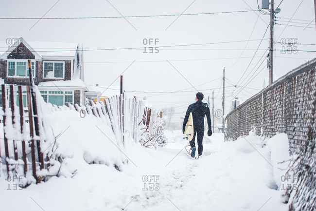 Surfer walks away from the beach during a winter snow storm in Maine