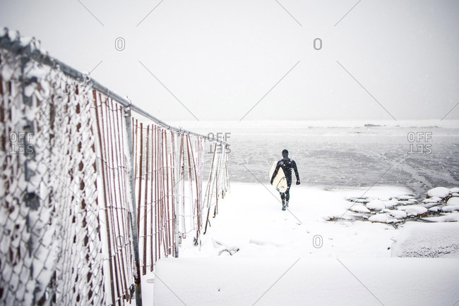 Surfer walks along Maine beach during winter snow storm
