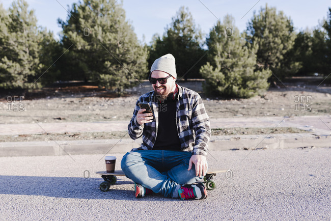 Modern young man sitting on a longboard looking at his mobile phone