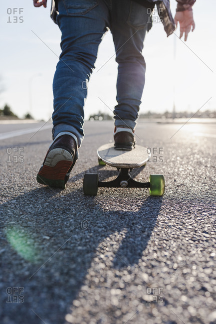 Anonymous man on longboard during golden hour