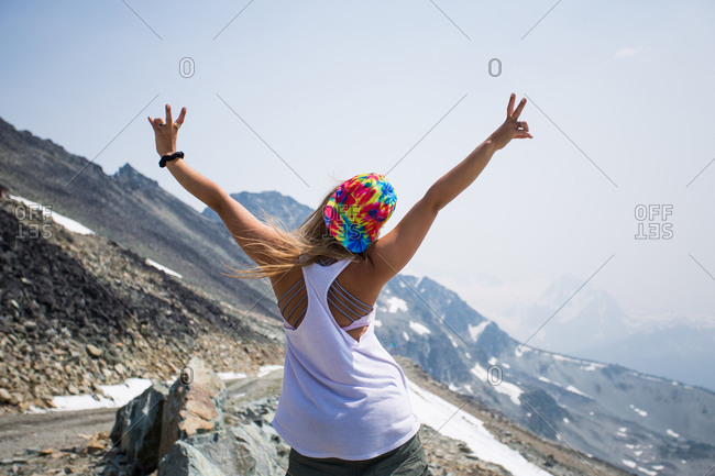 Girl Poses with Peace Sign On Top of Mountain in Summer