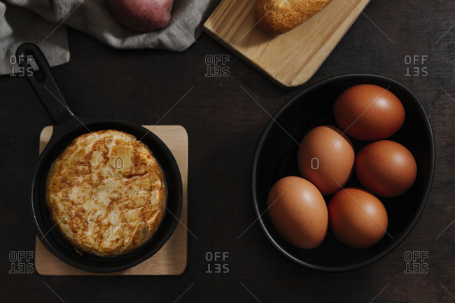 Spanish potato omelets with some fresh eggs shot from above over a wooden surface in a dark still life picture.