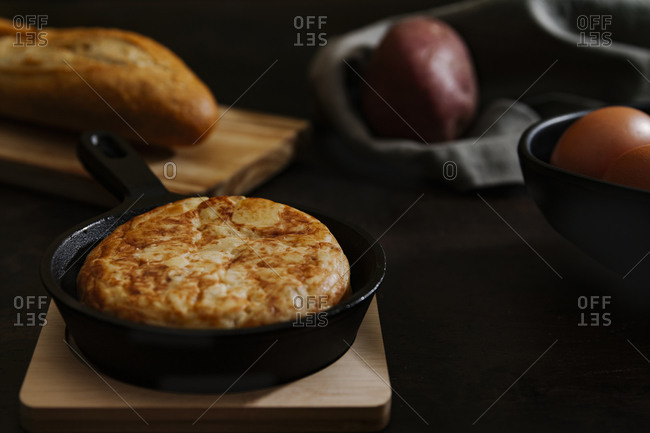Dark still life picture of a typical Spanish potato omelets in a pan with some bread and eggs in the background.