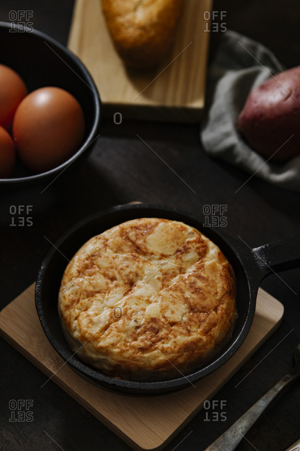 Spanish potato omelets with some fresh eggs shot from high angle over a wooden surface in a dark still life picture. Vertical image.