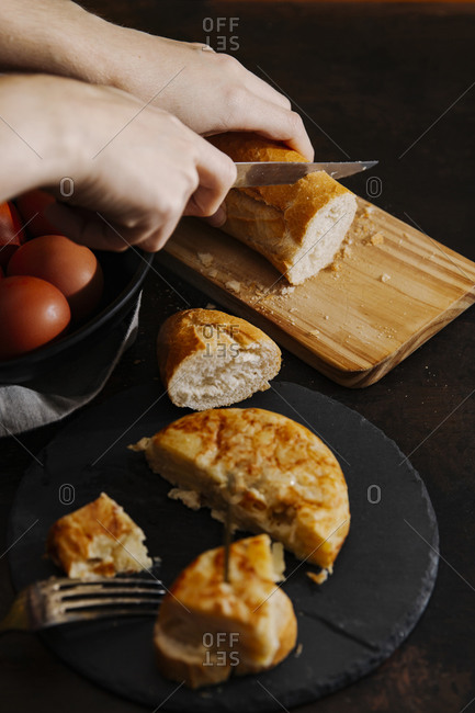 Spanish potato omelets sliced and served with bread. A woman is cutting some bread slices in the background.