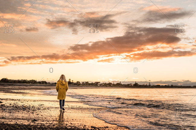 Preteen girl walking at dusk on a beach in winter