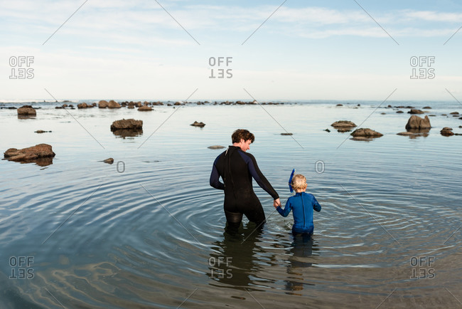 Father and young son preparing to snorkel