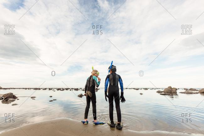 Tween siblings preparing to snorkel at beach in New Zealand