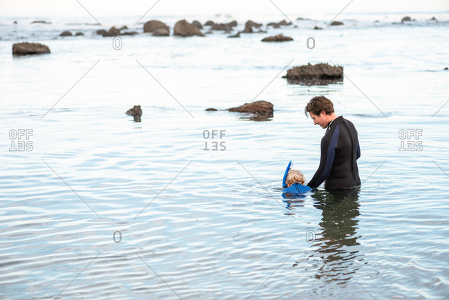 Father helping young child learn to snorkel