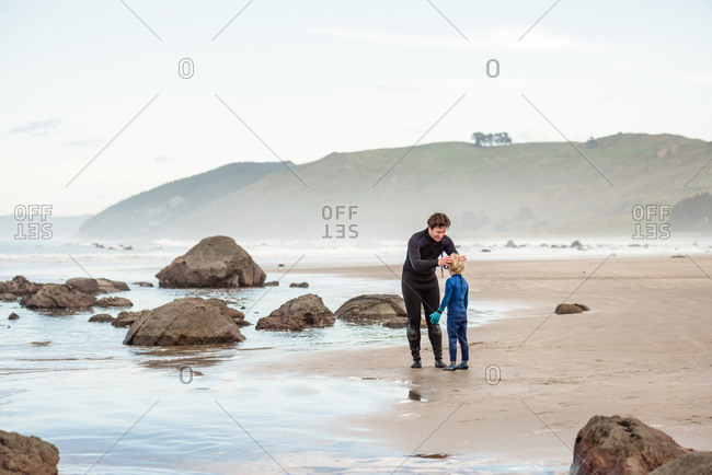 Dad helping small child put mask on at beach