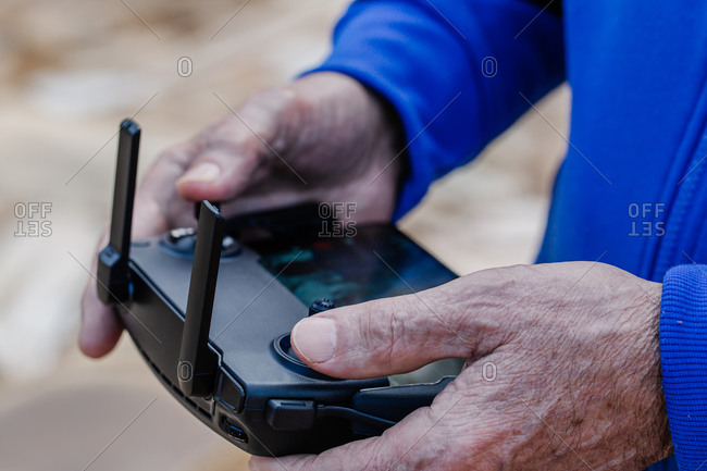 Close-up of old man operating drone using a remote control