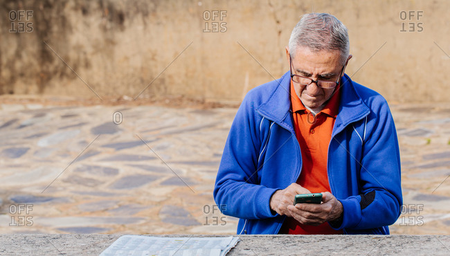 Senior man looking and touching screen of smartphone while sitting on park