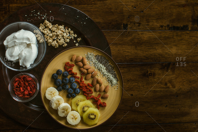 Healthy and delicious plate of fruit, nuts and seeds with yogurt and gogi berries