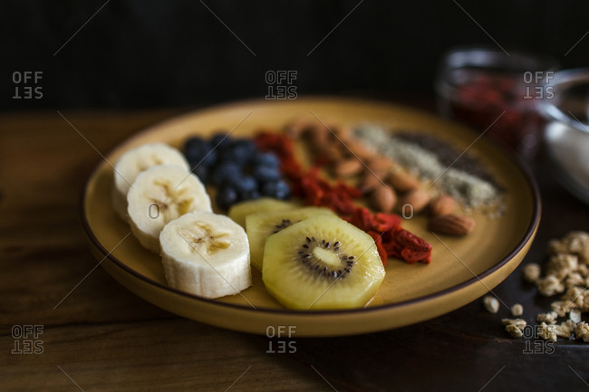 Healthy breakfast plate of fruit, berries and seeds with yogurt and granola