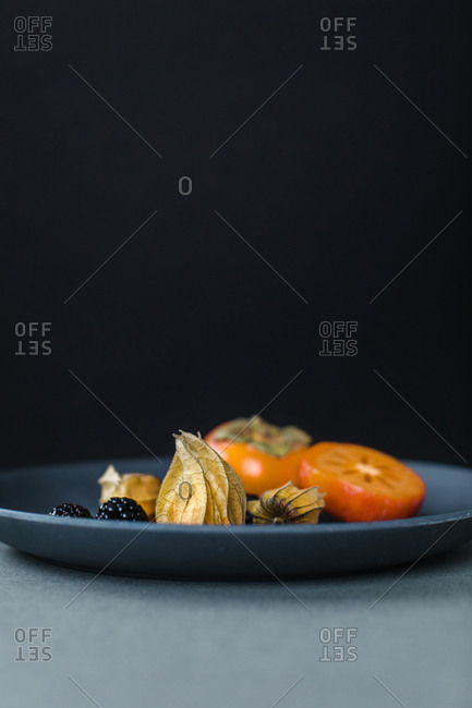 Physalis or cape gooseberries, blackberries and kumquats on a plate as a healthy snack