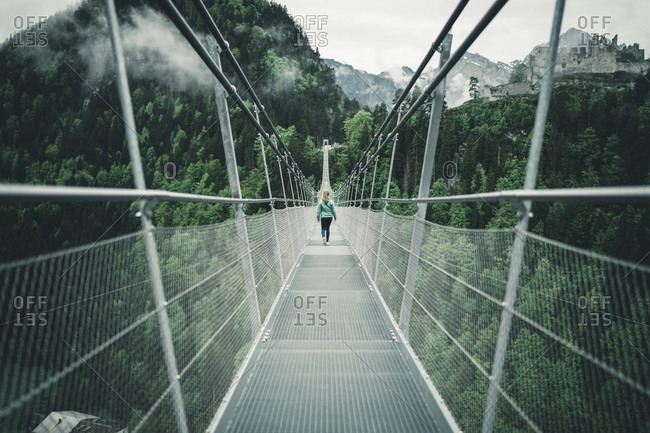 Young female hiking over suspension rope bridge in alpine environment