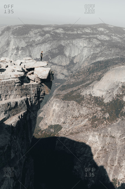 Young woman standing on top of Half Dome looking over a cliff