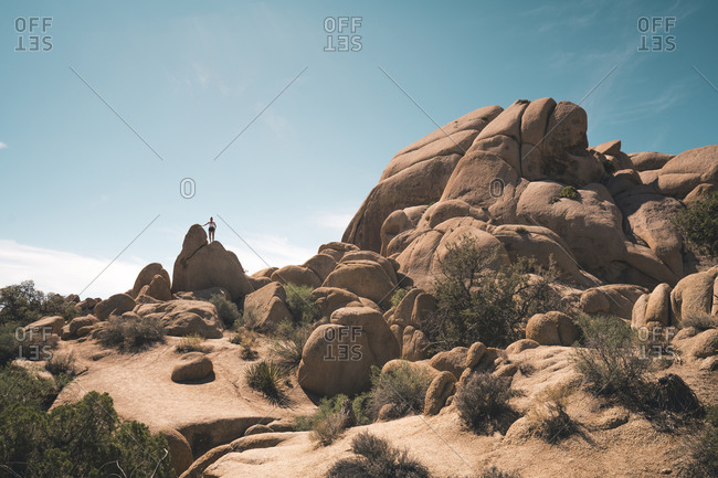 Woman climbing rock surreal formation against blue sky