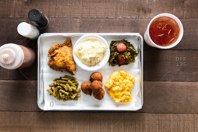 A tray of fried chicken, green beans, mac & cheese meal with sweet tea