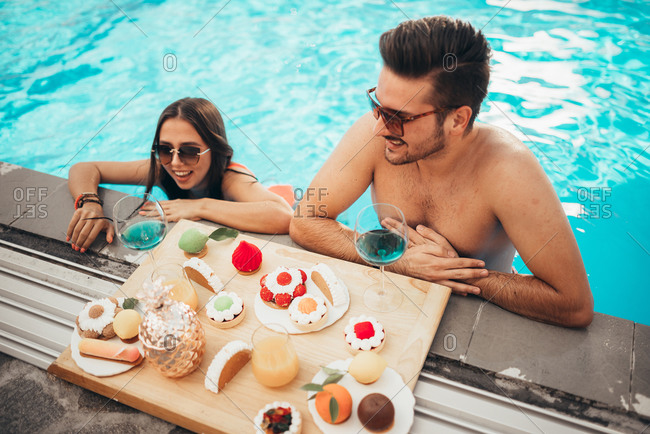 Beautiful couple enjoying tasty  food in pool during tropical vacation