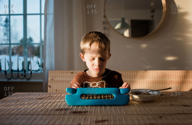 young boy playing in his iPad at home whilst eating breakfast
