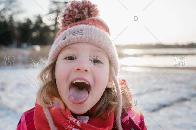 young girl catching snow on her tongue outside in winter