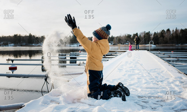 boy throwing snow up in the air whilst playing by the water in Sweden