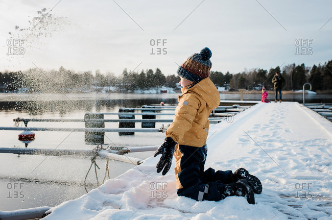 boy throwing snow up in the whilst playing outside by the sea