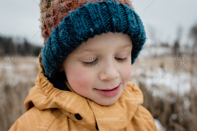 close up of a young boy looking down smiling whilst playing outside