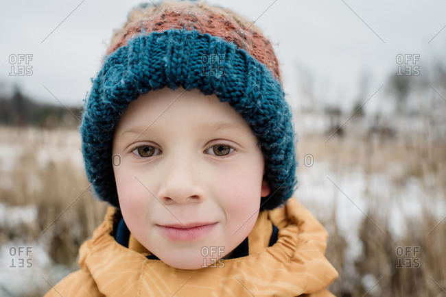 portrait of a young boy looking whilst playing outside in winter