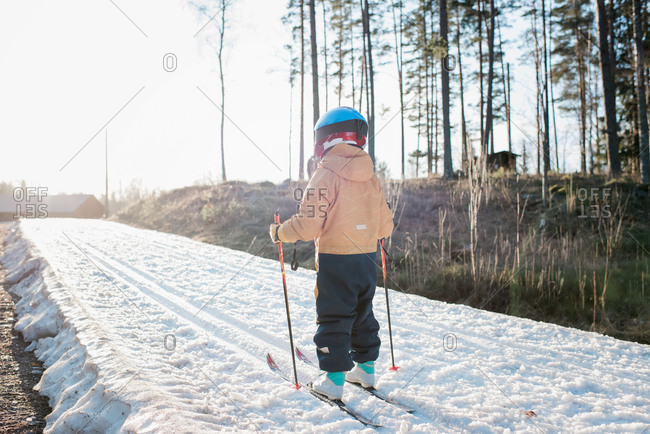 young boy cross country skiing in Sweden at sunset