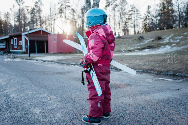 young girl holding cross country skis walking to the slopes in Sweden