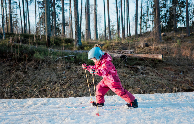 young girl cross country skiing in winter at sunset in Sweden