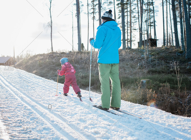 young girl cross country skiing with her dad in Sweden at sunset
