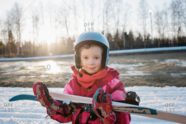 portrait of a young girl holding her cross country skis at sunset