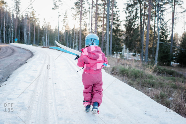young girl carrying cross country skis on a slope in Sweden