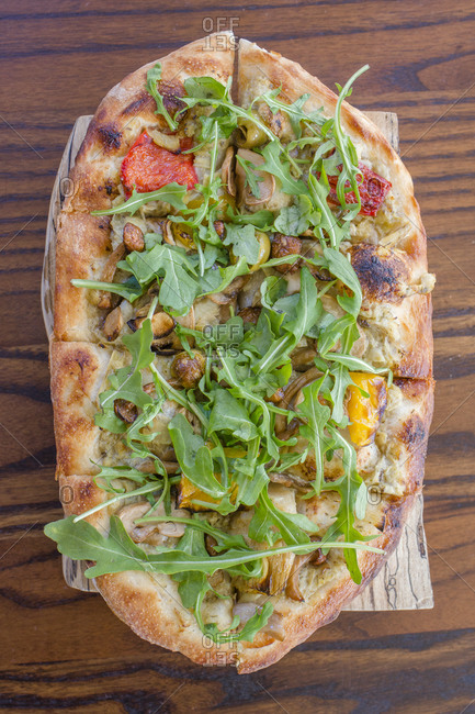 Close-up view of an Italian vegetable flatbread on a wooden board