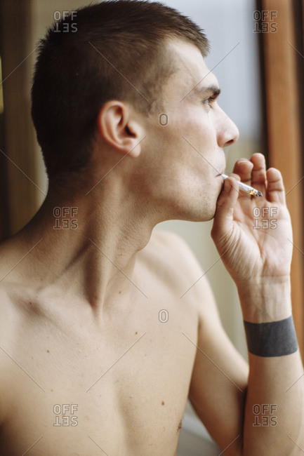 A side profile close-up portrait of a young man smoking cigarette