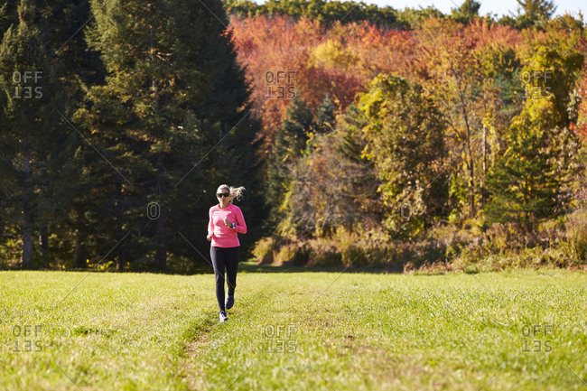 A woman running on a trail on a nice autumn day.