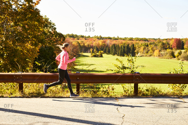 A woman running down a country road on a fall day.