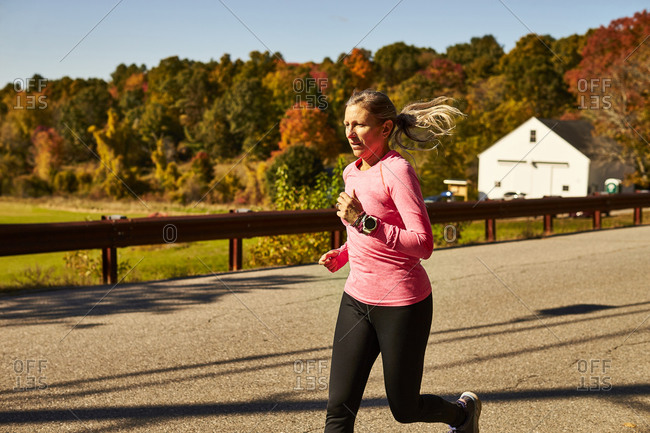 A close up of a woman running down a country road on a fall day.
