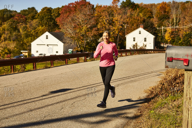 A woman runs down a country road on a autumn day.
