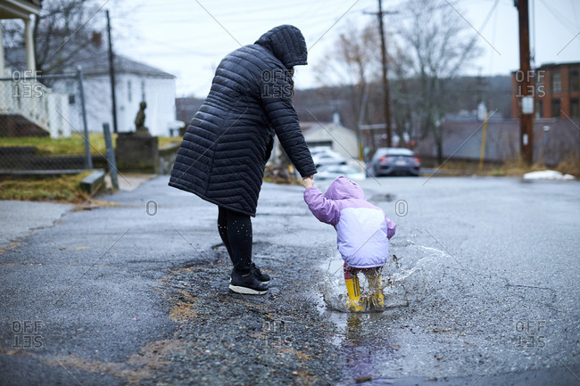 A mother and child having fun splashing in puddles on a rainy day.