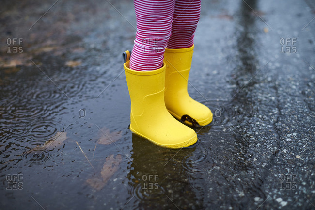 A close of up a child's rain boots in a puddle.