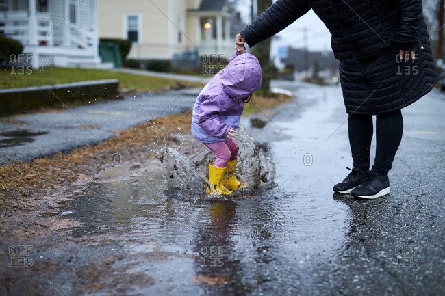 A little girl having fun splashing in puddles on a rainy day.