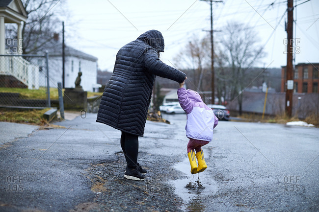 A mother and child having fun jumping in puddles.