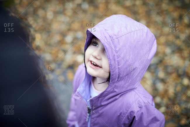 A happy portrait of a little girl outdoors in the rain.